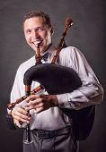 foto of bagpiper  - Smiling musician playing the Spanish bagpipes in the studio on a black background - JPG