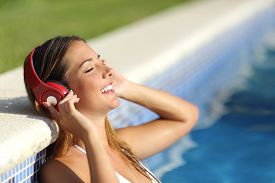 pic of bathing  - Relaxed woman listening to the music with headphones bathing in a pool - JPG
