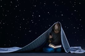 picture of boys night out  - Little boy reading book at night under the blanket - JPG