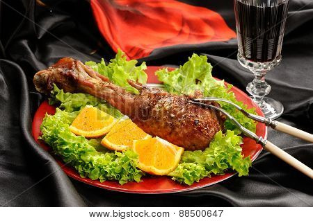 Roasted Turkey Drumstick With Orange And Lettuce On Black And Red Satin Cloth