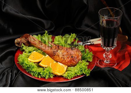 Roasted Turkey Drumstick With Orange, Lettuce And Red Wine On Black Satin Cloth With Copyspace