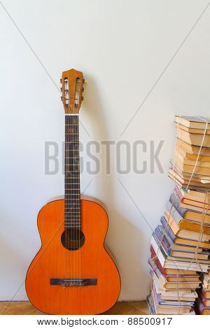 Orange Acoustic Guitar And A Pile Of Old Dusty Books.