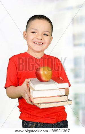 Happy little boy in red t-shirt carrying books and red apple