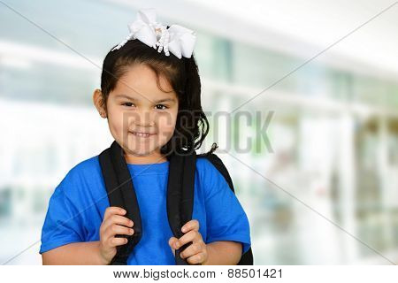Little schoolgirl in blue t-shirt going to school