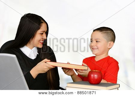 Young teacher handing a book to her student