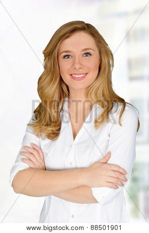 Young blonde woman standing with hands crossed
