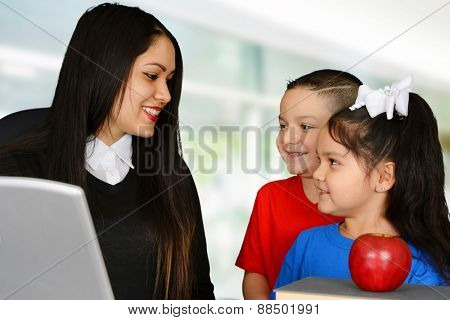 Young teacher talking to boy and girl