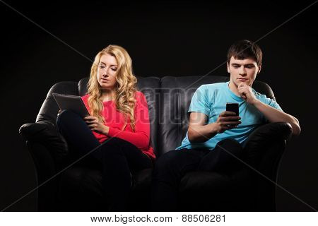 Boy and girl sitting separately with a smarthones. Disinterest, apathy and alienation concept.