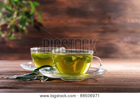 Cups of green tea on table on wooden background