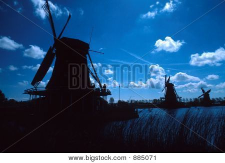 Silhouettes Of Windmills With White Clouds And Blue Sky.