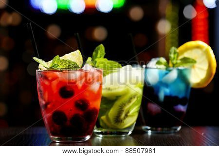 Glasses of cocktails in bar on bright blurred background