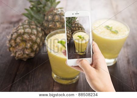 Taking Photo Of Pineapple Smoothie On Wooden Table