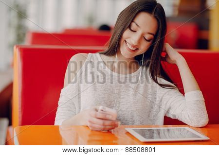 Beautiful Young Girl Enjoys Phone And Tablet