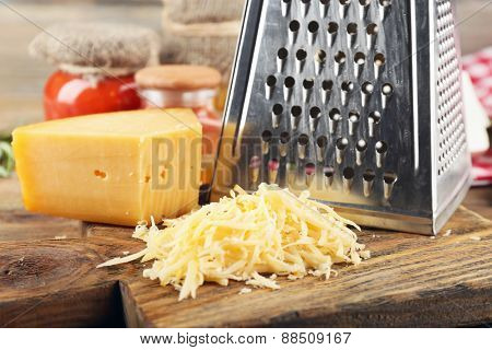 Grated cheese on wooden cutting board, closeup