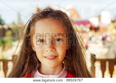 Pretty little girl smiling in a park close up