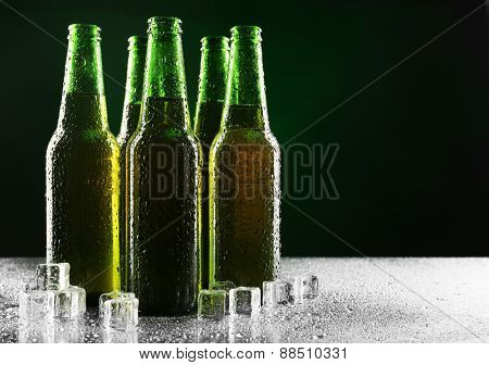 Glass bottles of beer with ice cubes on dark background