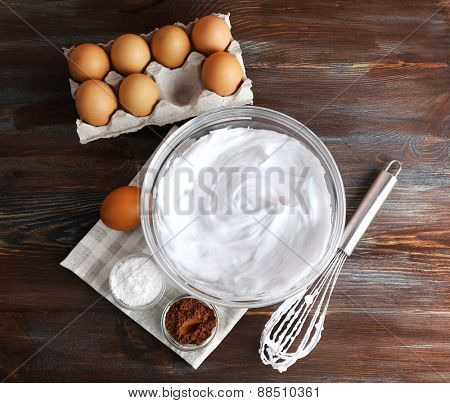 Whipped egg whites and other ingredients for cream on wooden table, top view