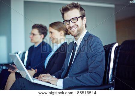 Happy businessman looking at camera while typing at seminar