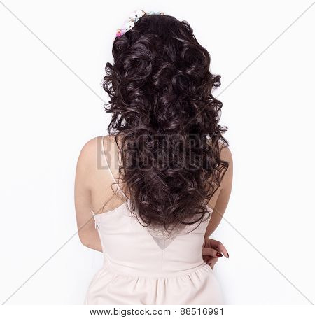 beautiful girl make her hair curls on long black hair decorated with a wreath of flowers