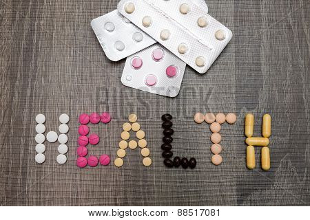 The Word Health Written With Pills On A Wooden Background.