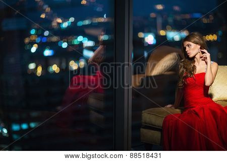 Beautiful young girl in a red dress in the apartment