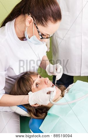 Doctor woman drills her patient tooth