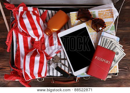 Packed suitcase of vacation items, top view