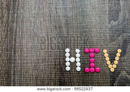 The Word Hiv(human Immunodeficiency Virus) Written Whith Pills On A Wooden Background.