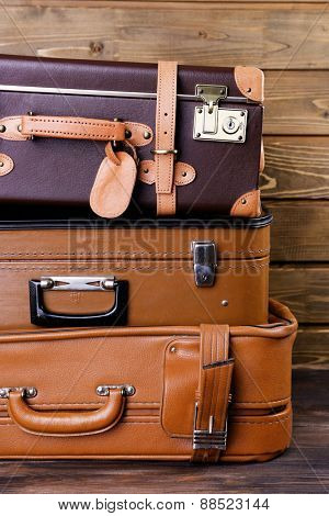 Stack of suitcases on wooden background