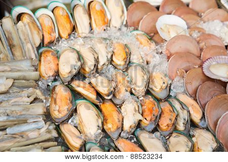cooking, asian kitchen, sale and food concept - chilled oysters or seafood on ice at street market