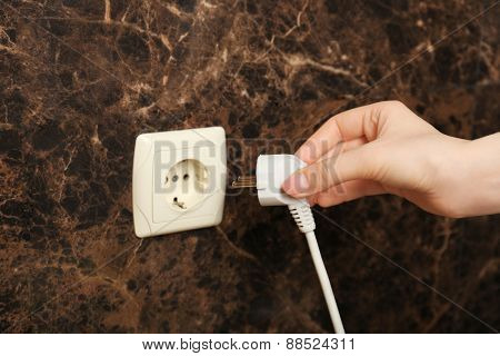 Hand putting plug in electricity socket close up