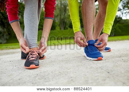 fitness, sport, friendship and lifestyle concept - close up of couple tying shoelaces outdoors