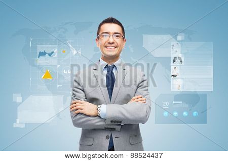 business, people, development and technology concept - happy smiling businessman in suit working with virtual screens over blue background