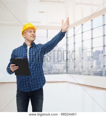 repair, construction, building, people and maintenance concept - smiling male builder or manual worker in helmet with clipboard pointing hand over empty flat background