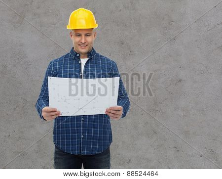 repair, construction, building, people and maintenance concept - smiling male builder or manual worker in helmet with blueprint over gray concrete wall background