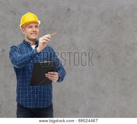 repair, construction, building, people and maintenance concept - smiling male builder or manual worker in helmet with clipboard taking notes over gray concrete wall background