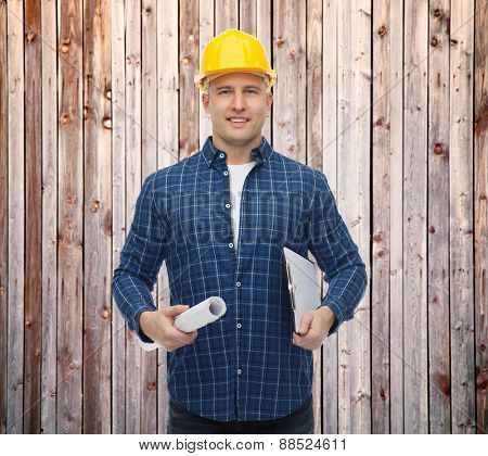 repair, construction, building, people and maintenance concept - smiling male builder or manual worker in helmet with blueprint and clipboard over wooden fence background