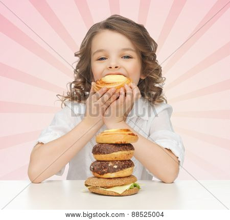 people, nutrition, childhood and health concept - happy little girl eating junk food over pink burst rays background