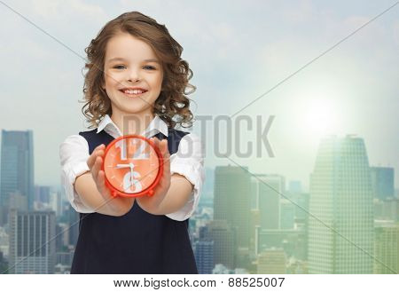 people, childhood, time and punctuality concept - happy girl with alarm clock over city background