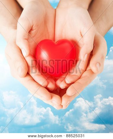 health, love and relationships concept - close up of couple hands with big red heart over blue sky and clouds background