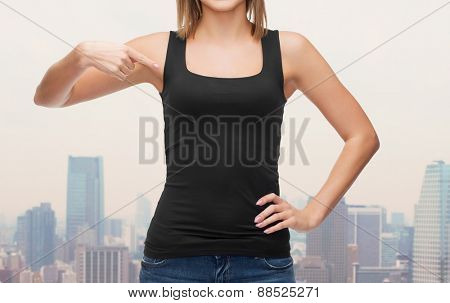 clothing design, fashion, advertisement and people concept - close up of woman in blank black tank top pointing finger at herself over city background