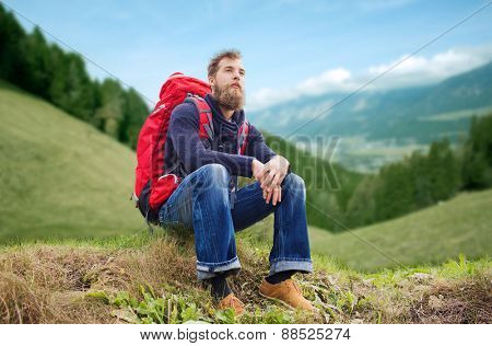 adventure, travel, tourism, hike and people concept - smiling man with red backpack sitting on ground over alpine hills background