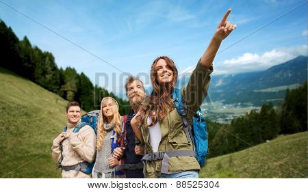 adventure, travel, tourism, hike and people concept - group of smiling friends with backpacks pointing finger over alpine hills background