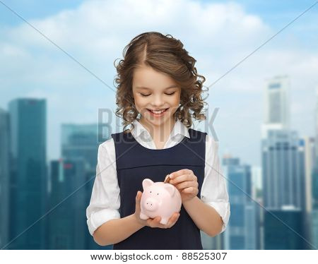 people, money, finances and savings concept - happy girl holding piggy bank and putting coin over city background