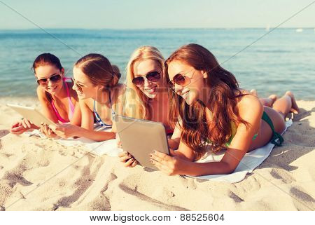 summer vacation, travel, technology and people concept - group of smiling women in sunglasses with tablet pc computers lying on beach