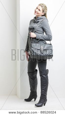 woman wearing grey clothes with a handbag