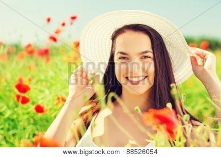 happiness, nature, summer, vacation and people concept - smiling young woman wearing straw hat on poppy field