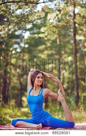 Flexible girl in sportswear doing yoga exercise for stretching in park