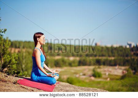 Meditating woman practicing yoga outdoors