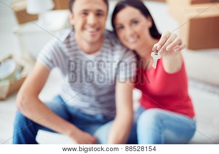 Young couple showing key from their house